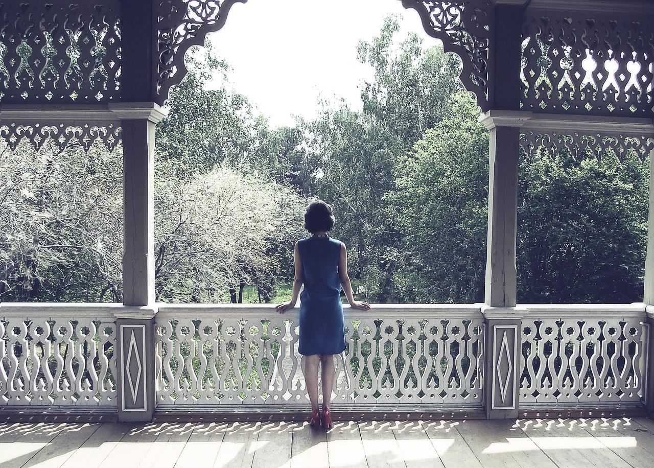 Frau im blauen Kleid steht in weißem Pavillon