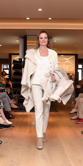 Model in beigem Outfit auf Laufsteg bei Modenschau im Geschäft