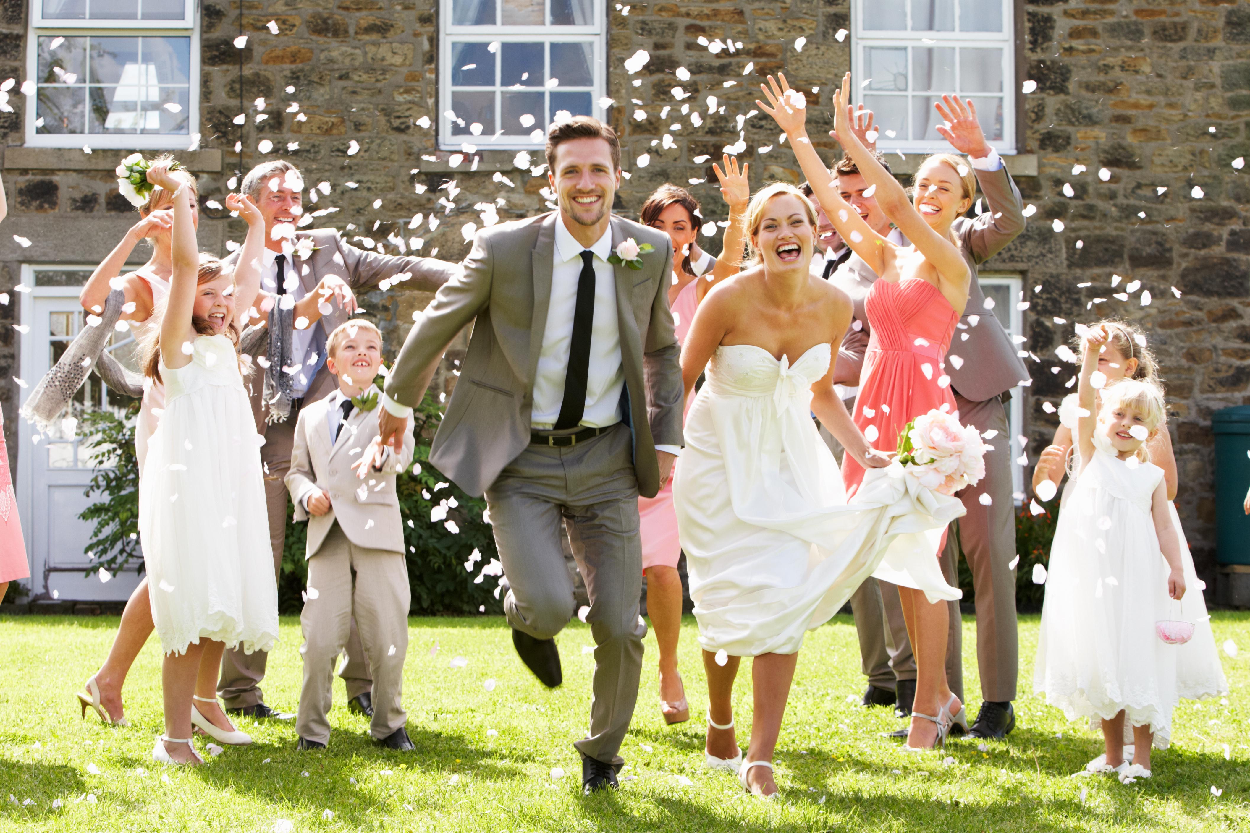 Gäste bewerfen Brautpaar mit Konfetti auf Hochzeitsfeier